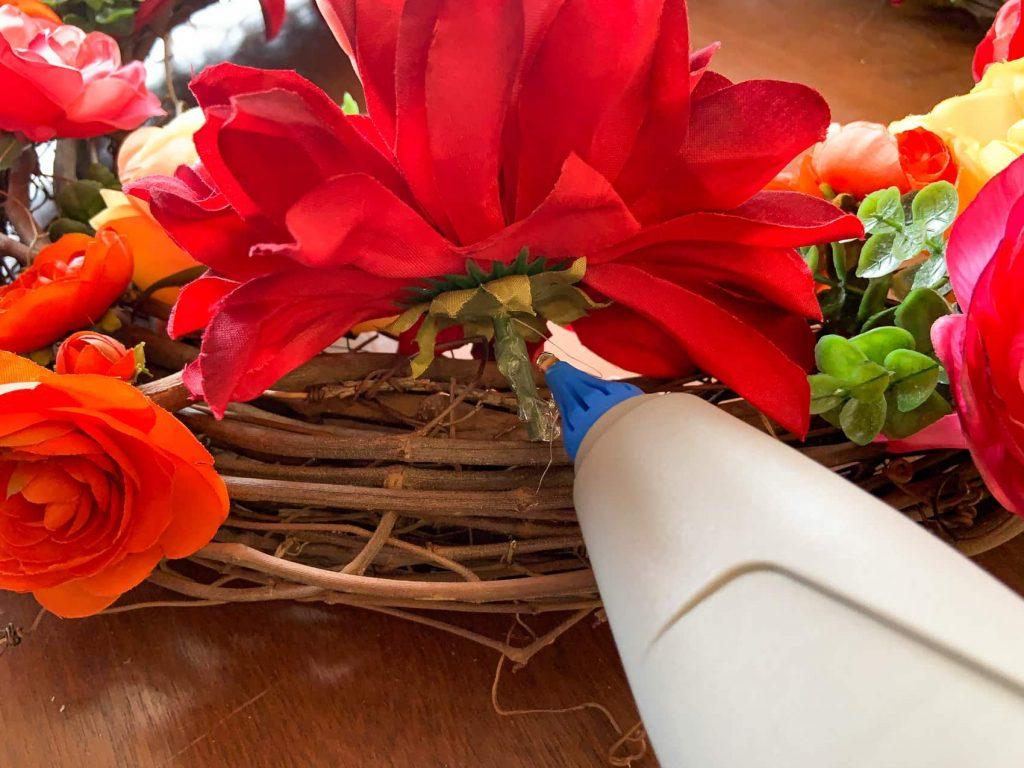 Hot glue flower stems into spring wreath