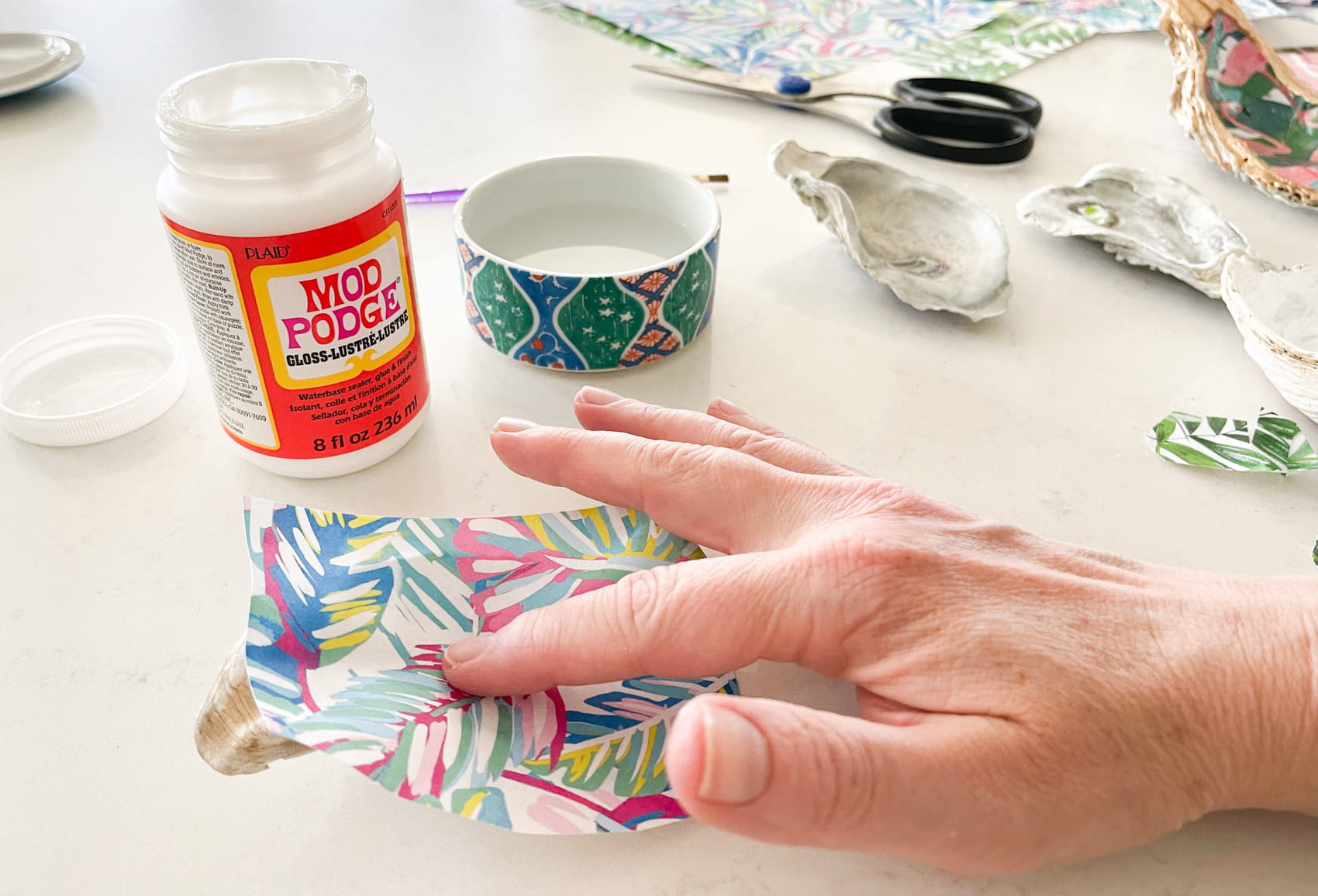 press decoupage paper into oyster shell