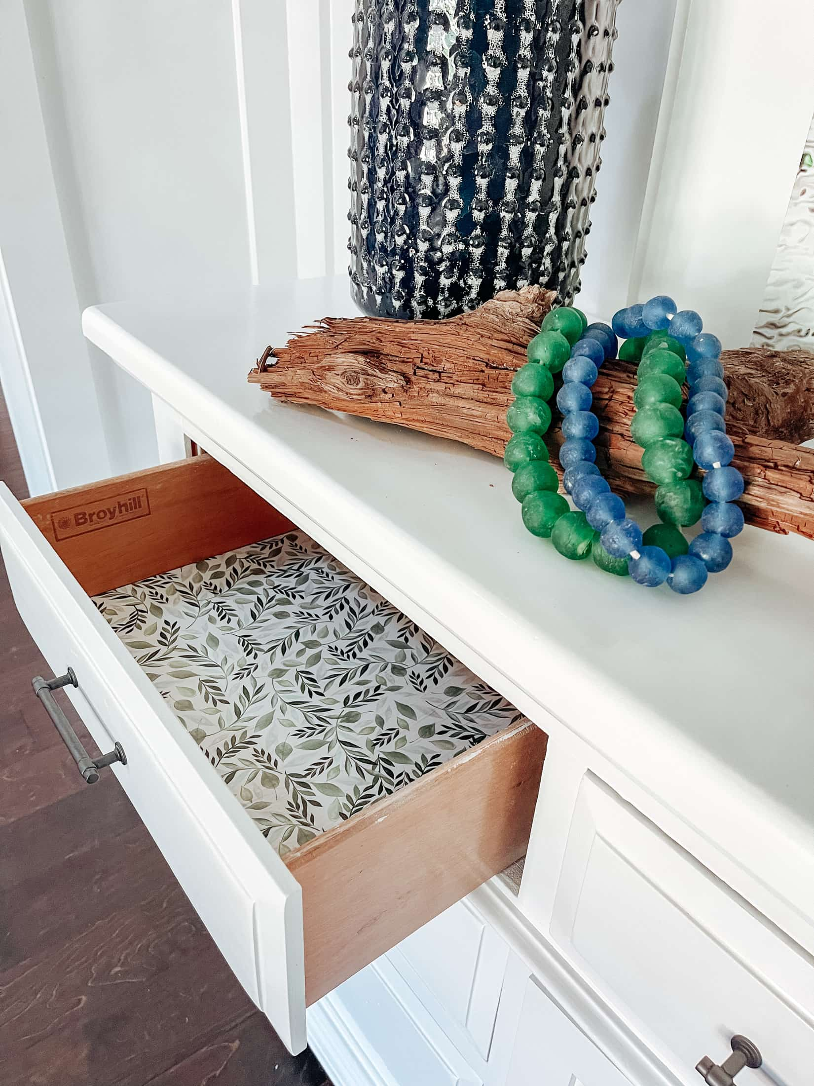 Line inside of drawers with wrapping paper for a pop of color on a refinished dresser